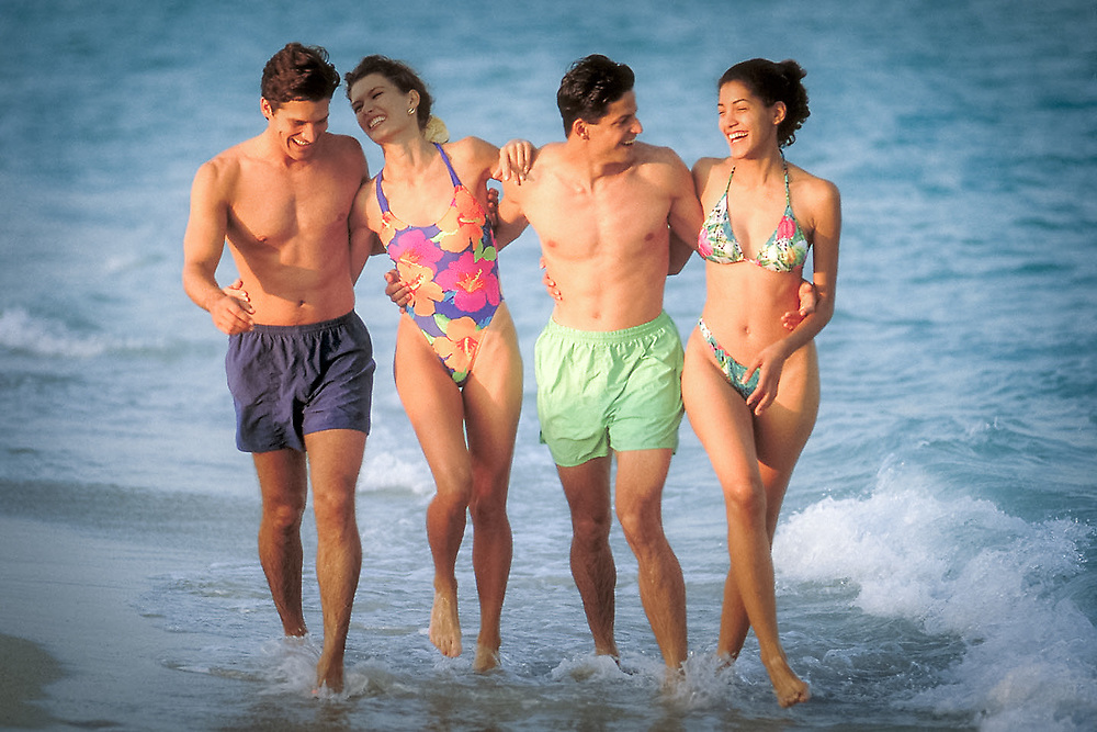 Two young couples strolling in surf along Miami Beach, Florida