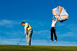 Taunton & Pickeridge Golf Club, Somerset, England - Simon Stevenson, PGA pro, demonstrating how to play golf in the wind, playing partner is lifted off his feet by a strong wind.