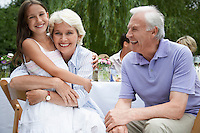 Grandparents with granddaughter (10-12) sitting at table in garden