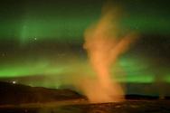 """Nächtliche Impressionen im geothermalgebiet mit den beiden Geysiren """"Geysir"""" und """"Strokkur"""" mit Sternen und grünen Nordlichtern im Südwesten von Island mitten auf dem Mittelatlantischen Rücken."""