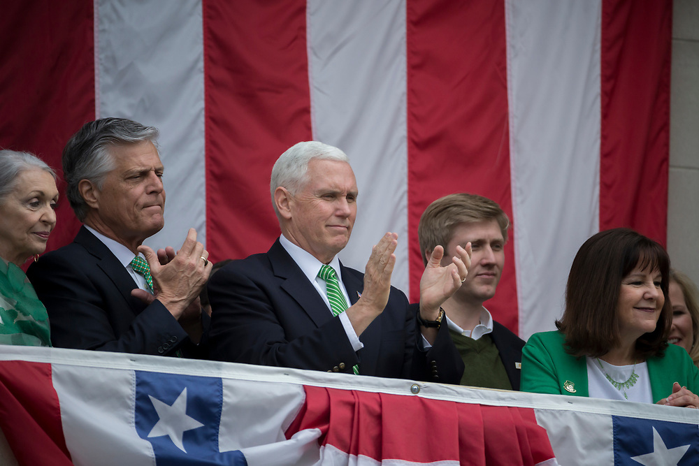 Vice President Mike Pence, center, and Savannah Mayor Eddie DeLoach, left, watch the St. Patrick's Day parade from the balcony at City Hall, Saturday, March 17, 2018, in Savannah, Ga. (AP Photo/Stephen B. Morton)