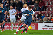 Craig Slater (#17) of Partick Thistle FC is pulled back by Sean Clare (#9) of Heart of Midlothian during the William Hill Scottish Cup quarter final replay match between Heart of Midlothian and Partick Thistle at Tynecastle Stadium, Gorgie, Edinburgh Scotland on 12 March 2019.