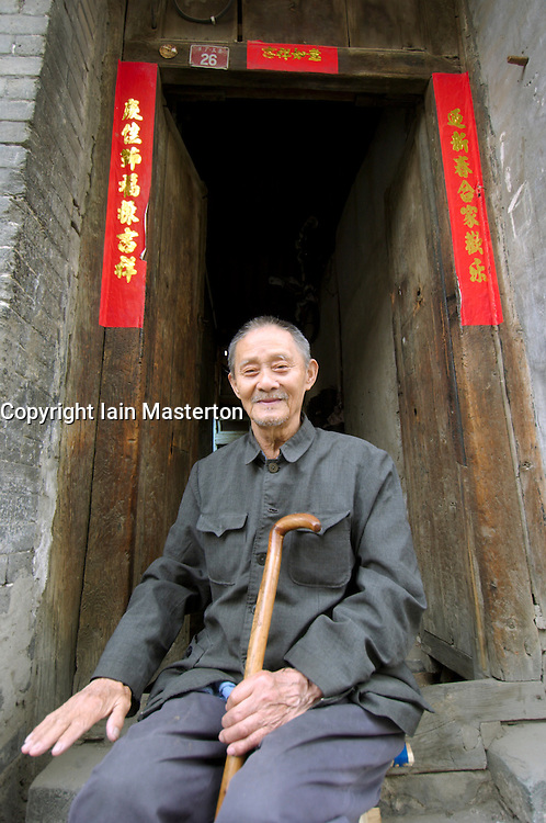 Elderly man sitting outside his old house in a traditional Beijing hutong or alleyway