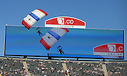 A member of the Frog-X parachute team parachutes into the stadium while the O.co Coliseum scoreboard shows video of him doing the jump before the Oakland Raiders 2015 NFL week 5 regular season football game against the Denver Broncos on Sunday, Oct. 11, 2015 in Oakland, Calif. The Broncos won the game 16-10. (©Paul Anthony Spinelli)