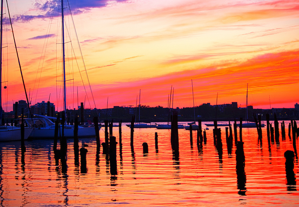 A red sky rises over pilings and  sailboats docked at Lewis Wharf in Boston Harbor, MA.