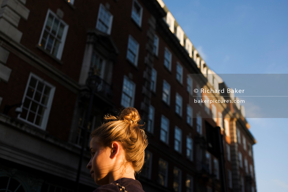 Young man stands at a road junction, about to cross along Piccadilly in late afternoon sunshine.