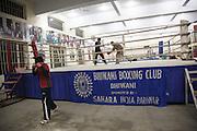 Le coach du Bhiwani Boxing Club Ms. Singh reste sur le ring à la fin de la journée pour entraîner une  jeune fille qui d'ici deux semaines aura une competition. En bas, une autre fille continue à s'entrainer dans le gymnase du Bhiwani Boxing Club à Bhiwani (Haryana, Inde)