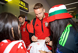 NANNING, CHINA - Monday, March 19, 2018: Wales' Chris Gunter signs autographs for supporters as the team arrive at Nanning International Airport for the 2018 Gree China Cup International Football Championship. (Pic by David Rawcliffe/Propaganda)
