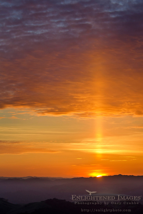 Sun Pillar and clouds at sunset over the Berkeley Hills, California