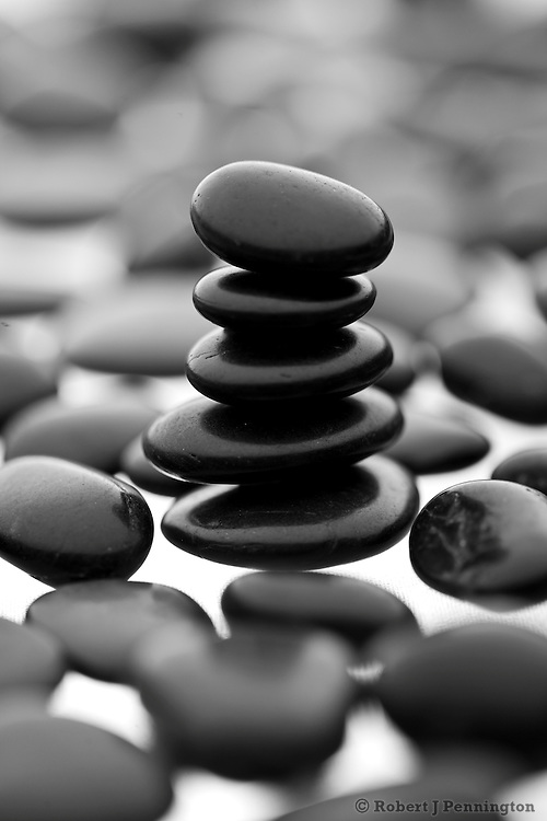 A cairn stack of small black stones within a shallow focus field of stones.