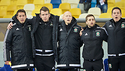 KIEV, UKRAINE - Easter Monday, March 28, 2016: Wales' sports science coach Adam Owen, Ronan Kavanagh, Paul Harris, masseur Chris Senior and staff stand for the national anthem before the International Friendly match against Ukraine at the NSK Olimpiyskyi Stadium. (Pic by David Rawcliffe/Propaganda)