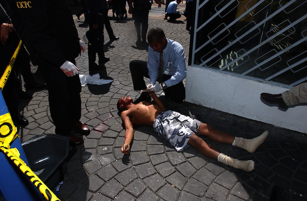A police officer takes the fingerprints of a man who was shot while attempting to rob El Banco Canarias de Venezuela, a bank in downtown Caracas, with 6 other men.  2 of the men were shot and killed during the attempted robbery.