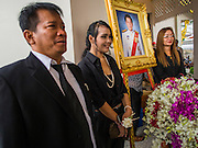 19 OCTOBER 2014 - BANG BUA THONG, NONTHABURI, THAILAND: Mourners pose for photos with Apiwan Wiriyachai's portrait at Apiwan's cremation at Wat Bang Phai in Bang Bua Thong, a Bangkok suburb, Sunday. Apiwan was a prominent Red Shirt leader. He was member of the Pheu Thai Party of former Prime Minister Yingluck Shinawatra, and a member of the Thai parliament and served as Yingluck's Deputy Prime Minister. The military government that deposed the elected government in May, 2014, charged Apiwan with Lese Majeste for allegedly insulting the Thai Monarchy. Rather than face the charges, Apiwan fled Thailand to the Philippines. He died of a lung infection in the Philippines on Oct. 6. The military government gave his family permission to bring him back to Thailand for the funeral. His cremation was the largest Red Shirt gathering since the coup.     PHOTO BY JACK KURTZ