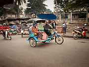 "Mar. 15, 2009 -- LUANG PRABANG, LAOS: A ""tuk-tuk"" (three wheeled taxi) carries a fare in the ""morning market"" in Luang Prabang. The morning market is primarily by local residents for groceries and daily needs. Most Laotians don't have refrigerators so the they shop daily for perishables. Luang Prabang is a UNESCO World Heritage Site and the spiritual capital of Laos. There are dozens of ""wats"" or temples and thousands of monks in the city. It is still the center of Buddhist education in Laos.  Photo by Jack Kurtz"
