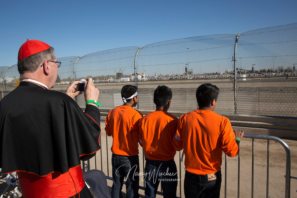 Cardinal Roger Mahony, retired archbishop of Los Angeles, photographs young men as they look out toward the Mass with Pope Francis Feb. 17 from the U.S. side of the border in El Paso, Texas. Minors under detention for entering the U.S. without documentation were among those situated on a levee north of the Rio Grande for the Mass the pope celebrated in Ciudad Juarez, Mexico. (CNS photo/Nancy Wiechec)
