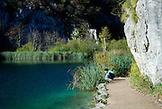 Child (9 years old) squatting on path looking into lake, Plitvice National Park, Croatia
