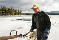 John J guides the ice blocks up the chute during the Rockywold-Deephaven Camp annual ice harvest on Wednesday morning.  (Karen Bobotas/for the Laconia Daily Sun)