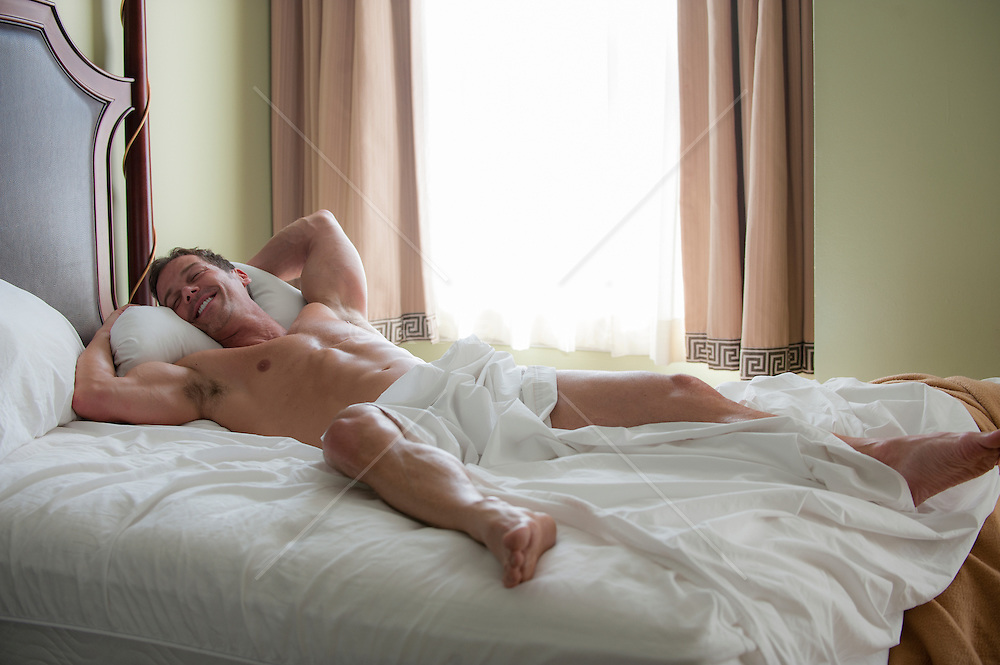 sexy man smiling while resting in bed without any clothes on.