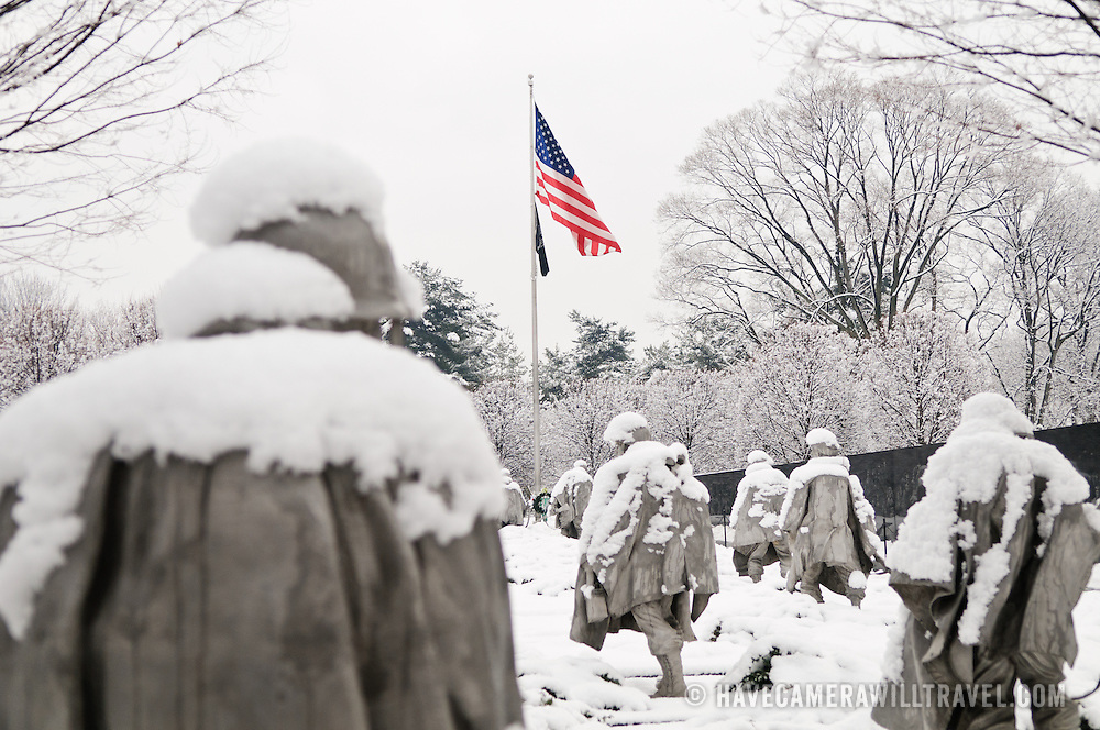 "The Korean War Veterans Memorial on the National Mall on a winter morning after heavy snow. The Korean War Veterans Memorial, unveiled in 1992, sits on the northwestern end of the National Mall, not far from the Lincoln Memorial. It consists of several elements designed by different people and groups. It has a triangular footprint with the main elements being ""The Column"" consisting of 19 stainless steel solders, each over 7 feet tall, and a reflective granite wall etched with the faces of thousands of Americans who lost their lives in the war. At one end of the triangle, behind the soldiers, is a grove of trees. At the other is a large American flag and a small Pool of Remembrance. Among the designers were Frank Gaylord (the soldiers) and Louis Nelson (the reflecting granite wall)."