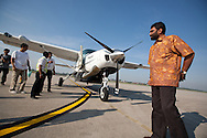 Kumi Naidoo, executive director of Greenpeace International (wearing yellow batik shirt), arrives for a short fueling stop in Palembang, whilst flying in a plane over Southern Sumatra province to witness first hand the beauty of the forest, and the encroaching destruction of it., in southern Sumatra province, Indonesia, Saturday 16th October 2010. The plantations for paper are owned by Asia Pulp and paper, a subsidiary of Sinar Mas.