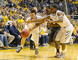 West Virginia Mountaineers guard Chase Connor (10) and West Virginia Mountaineers guard Juwan Staten (3) go for a loose ball against the Texas Longhorns during the first half at the WVU Coliseum.