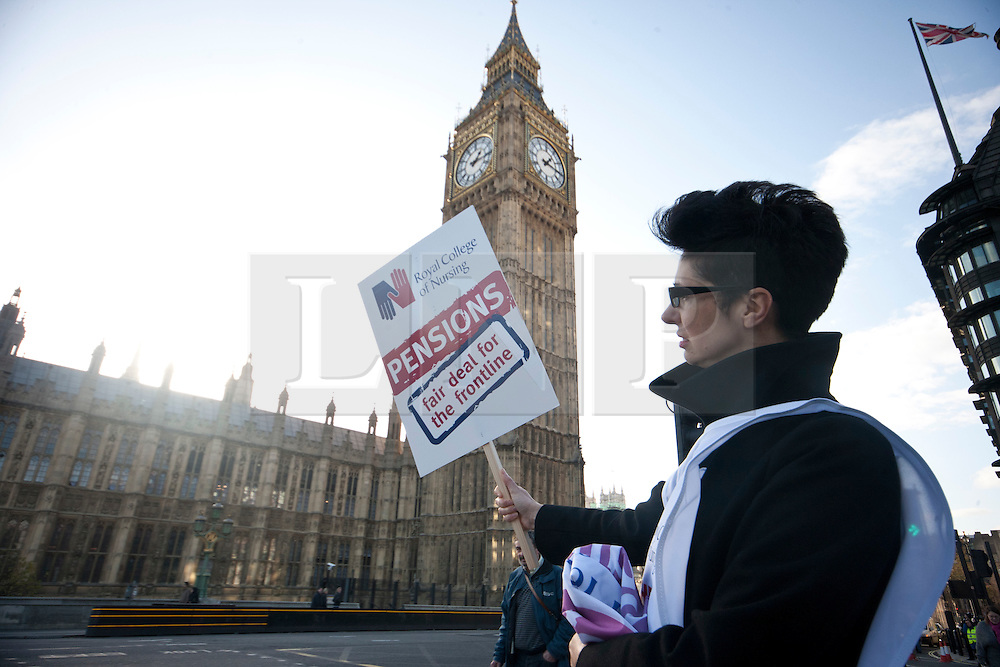 © licensed to London News Pictures. London, UK 30/11/11. A medical worker waits her friends in front Houses of the Parliaments to join the main march in London to demonstrate the pension cuts and tax rises. Photo credit: Tolga Akmen/LNP