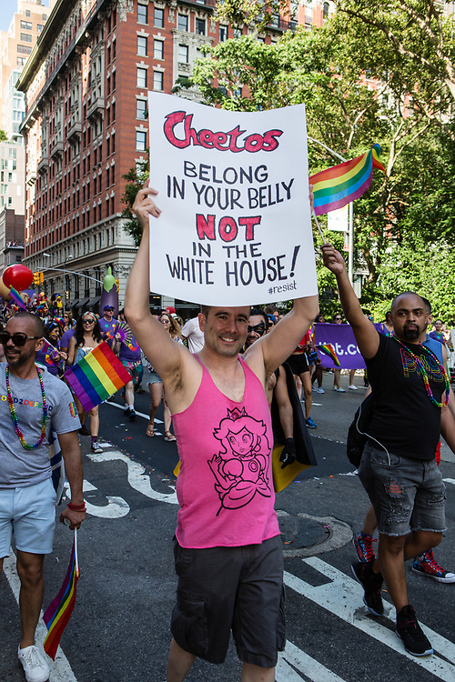 "New York, NY - 25 June 2017. New York City Heritage of Pride March filled Fifth Avenue for hours with groups from the LGBT community and it's supporters. An anti-Trump marcher carries a sign reading ""Cheetos belong in your belly not in the White House."""