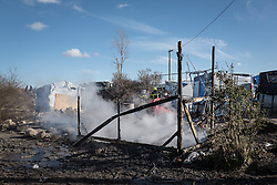 © London News Pictures. Calais, France. 04/03/16. The smouldering remains of a shelter in the Calais 'Jungle'. French authorities are clearing the southern half of the Calais 'Jungle' camp, which charities estimate to contain 3,500 people. Photo credit: Rob Pinney/LNP