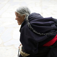 APRIL 5, 2012 : an elderly Tibetan woman walks inside the alleys of Labrang monastery.