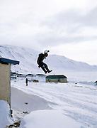 Un jeune Inuit s'amuse à sauter dans la neige à partir d'un toit..Village de Kangiqsujuaq, Nunavik.