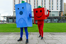 © Licensed to London News Pictures. 25/10/2019. LONDON, UK. Men dressed as (L to R) Mr Grumpy and Mr Strong from the Mr Men join other cosplayers from all over the world attending the opening day of the bi-annual MCM Comic Con event at the Excel Centre in Docklands.  The event celebrates popular culture such as video, games, manga and anime providing many attendees with the opportunity to dress up as their favourite characters.  Photo credit: Stephen Chung/LNP