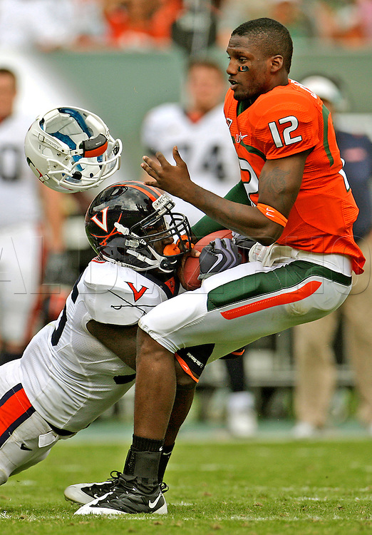 Virginia linebacker Cam Johnson (56) face masks and rips the helmet off Miami's quarterback Jacory Harris (12) in the third quarter as the University of Miami host the Virginia Cavaliers at Land Shark Stadium on Saturday November 7.