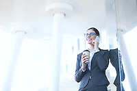 Businesswoman using cell phone while holding disposable cup outdoors