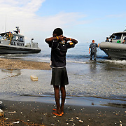 100119-N-5345W-041.BONEL, Haiti (Jan. 19, 2010).A Haitian boy watches from the shore edge as rigid-hull inflatable boats (RHIBs) from the amphibious dock landing ships USS Fort McHenry (LSD 43) and USS Carter Hall (LSD 50) arrive ashore, along with several landing craft carrying manpower and heavy equipment as Sailors and Marines establish their operating base at New Hope Mission in Bonel, Haiti. The multi-purpose amphibious assault ship USS Bataan (LHD 5) is on station in Haiti along with USS Fort McHenry (LSD 43), USS Gunston Hall (LSD 44), and USS Carter Hall (LSD 50) as the Bataan Amphibious Relief Mission in support of Operation Unified Response, a joint operation providing military support capabilities to civil authorities to help stabilize and improve the situation in Haiti following a 7.0 magnitude earthquake that devastated the island nation. (U.S. Navy photo by Mass Communication Specialist 2nd Class Kristopher Wilson/Released)