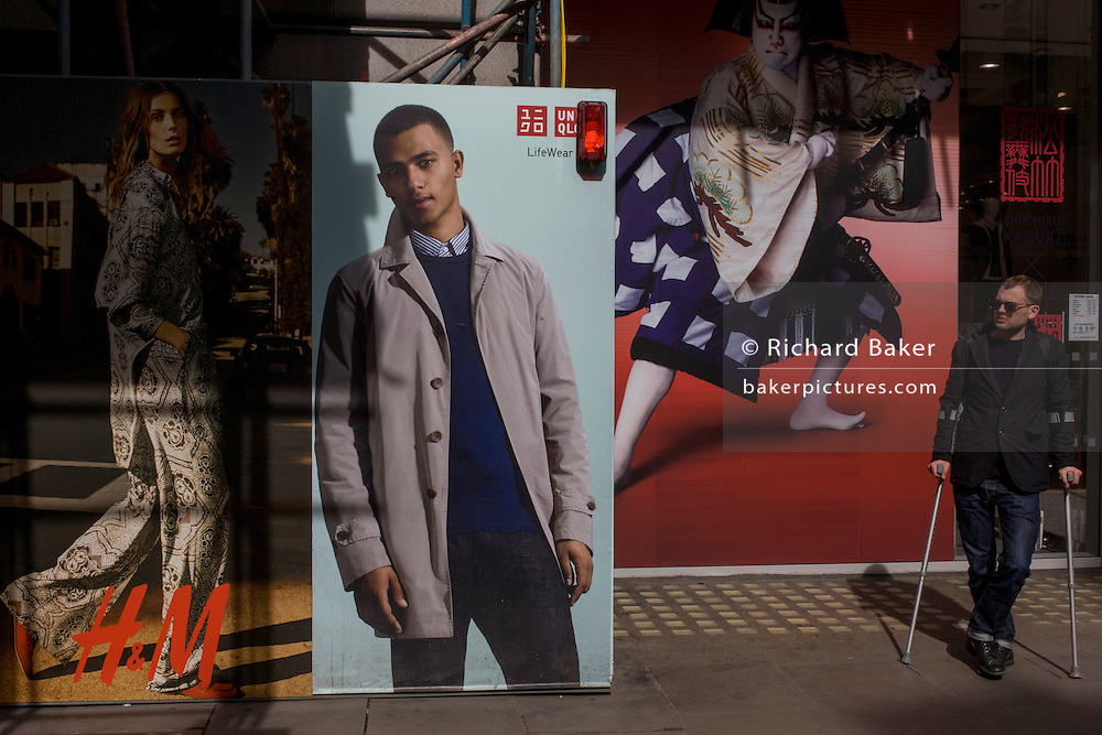 Man with walking crutches in front of H&M menswear poster outside central London shop.