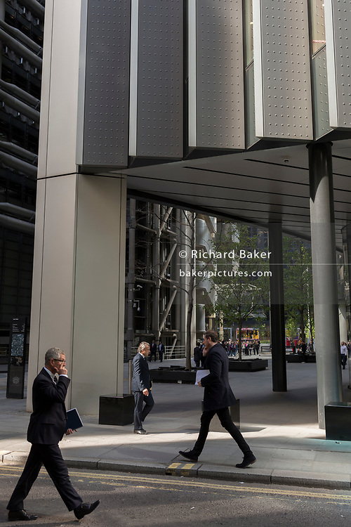 Financial industry people walk through reflected light from a nearby skyscraper in the City of London, the capital's financial district aka the Square Mile, on 17th May 2018, in London, UK.
