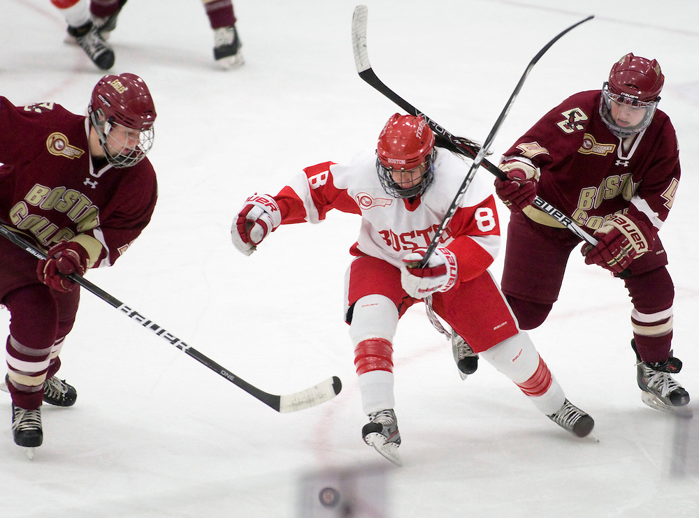 1/25/12 7:21:15 PM -- Boston, Massachusetts..Boston University forward Kayla Tutino, center, drives for the puck in between Boston College forwards Taylor Wasylk, left, and Melissa Bizzari, right, as BU took on BC at the Walter Brown Arena in Boston, Massachusetts on Wednesday, January 25, 2012.  BU won, 6-0, to bring their record with BC to two wins and one loss. ..Photo by Brooks Canaday for Boston University Photography