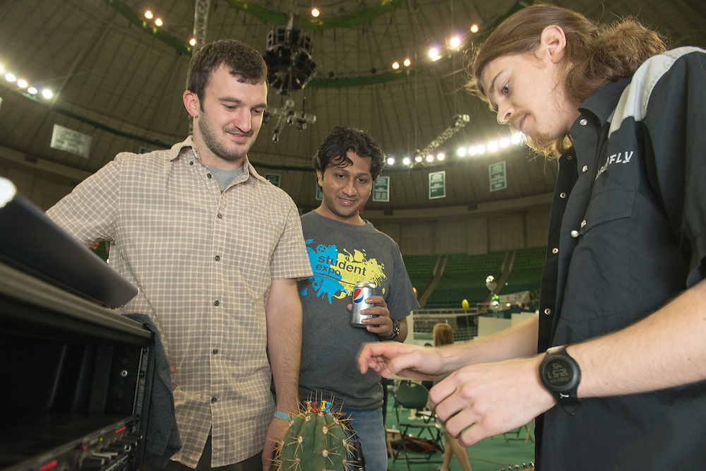 Ohio University students Travis Raffle (Left) and Naveen Nagaraj (Center) react to a demonstration by John Salutz (right) on how music can be created by plucking the thorns on a cactus at the Student Expo at the Convocation Center on Thursdau, April 11, 2013. . Photo by Ben Siegel
