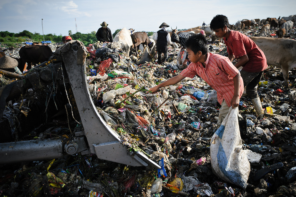 Taupik, 14, working in front of a bulldozer on the 'Trash mountain', Makassar, Sulawesi, Indonesia.  Many of the pickers follow the bulldozers as they move newly dumped waste, uncovering plastic and metal for recycling in the process.