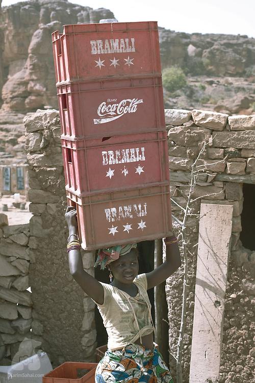 girl balancing crates on her head dogon country mali karim sahai