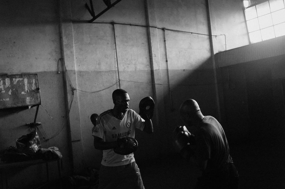 NAIROBI, KENYA - NOVEMBER 09, 2011: Volunteer boxing coach Hassan Abdulkadir Salim (left) trains with members of the Kibera Olympic Boxing Club at the Joseph Kangethe Social Hall in Kibera slum. <br /> <br /> Within Kenya's progressive youth culture is the Kibera Olympic Boxing Club, a group of low-income adolescents from the slum whose leader uses boxing as a way to engage with idle youth. The group's ethnic diversity is remarkable given Kenya's 2008 post-election violence in which people from several tribes were forced violently out of slums. Together, these boxers represent a nascent trend of cross-tribe brotherhood in a healing nation.
