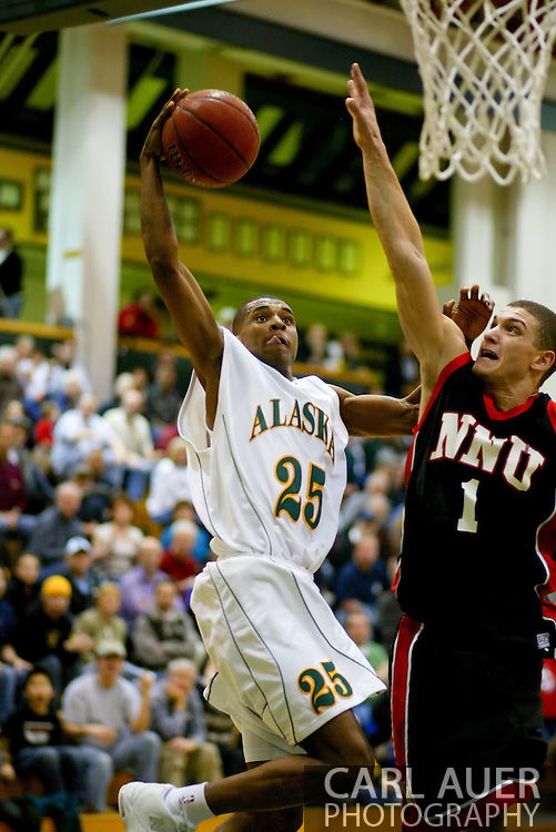 1/13/2006: Senior guard Eric Draper (25) of the UAA Seawolves heads up hard to the hoop to attempt a dunk over Tim Ireland of the Northwest Nazarene University Crusaders in the Alaska Anchorage comeback victory over Northwest Nazarene, 60-57, in men?s basketball action at the Wells Fargo Sports Complex on Saturday.