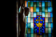 The altar crucifix against a stained glass window depicting a cross and crown on Wednesday, May 13, 2020, at Trinity Lutheran Church, Millstadt, Ill. LCMS Communications/Erik M. Lunsford