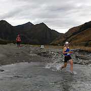 Runner Sue Mavor crosses  Moke Creek on the Ben Lomond High Country Station during the Pure South Shotover Moonlight Mountain Marathon and trail runs. Moke Lake, Queenstown, New Zealand. 4th February 2012. Photo Tim Clayton