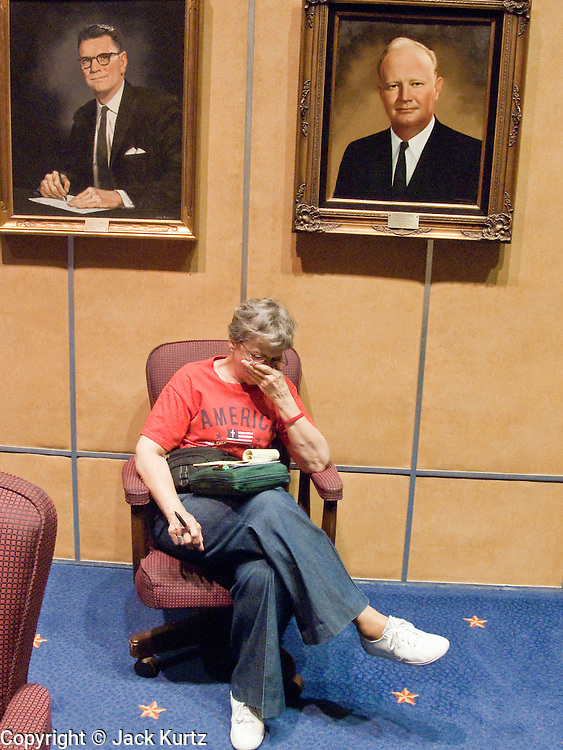 07 MAY 2009 -- PHOENIX, AZ: Alice Wells (CQ) from Ahwatukee prays under the portraits of former Senate Presidents Clarence Carter (LEFT) and Marshall Humphrey in the Senate chambers during the National Day or Prayer services at the State Capitol in Phoenix Thursday. About 30 people came to the capitol to pray for government officials at the desks of legislators.   Photo by Jack Kurtz
