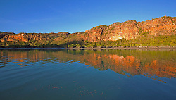 The stunning red cliffs of the Hunter River are reflected in the water in late afternoon.