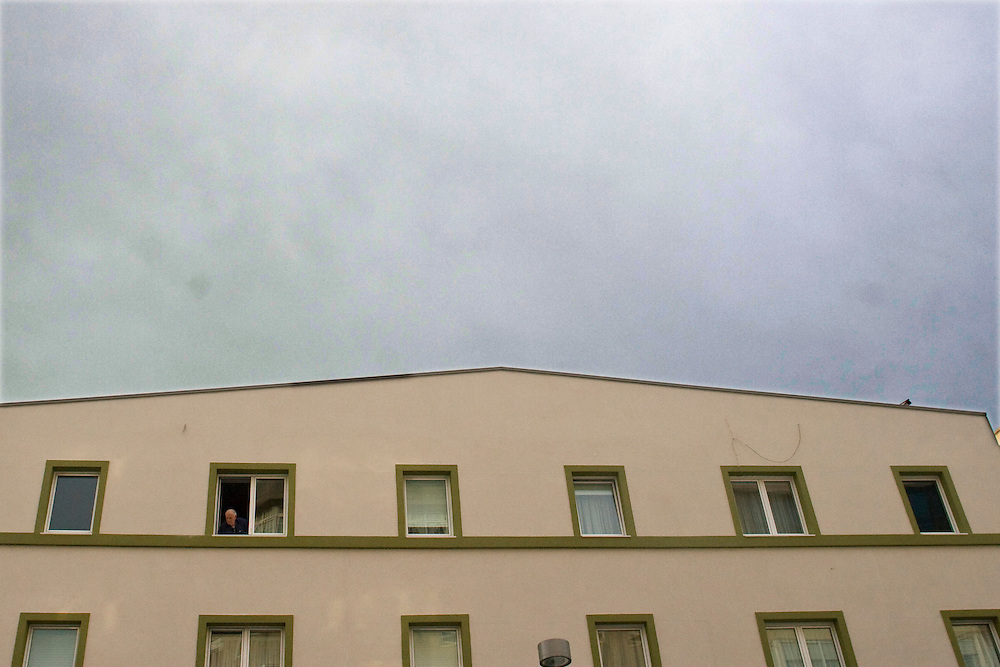 (A Coruña, Spain - January 20, 2010) - Will Nunnally takes some street photos around A Coruña on his birthday. A man looks out of the fourth story window of a refurbished apartment in La Bañaeu...Photo by Will Nunnally / Will Nunnally Photography