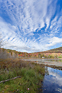 Fall foliage and spectacular clouds at Wheeler Pond in Barton, Vermont