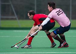 Southgate's Shaun Comley is tackled by Adam Jolly of Teddington. Southgate v Teddington - Men's Hockey League East Conference, Trent Park, London, UK on 21 February 2016. Photo: Simon Parker