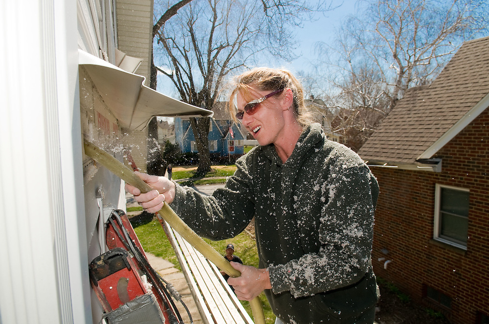 Shelle Davis of ABA Insulation works on blowing cellulose insulation into the walls to help weatherize a home on Woodbury Ave. in Cleveland on Thursday, April 2, 2009. ABA Insulation is one of many companies who are trying to capitalize on economic stimulus money. Jason Miller